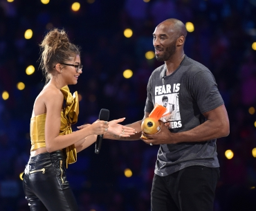 Actress Zendaya (L) presents the Legend award to honoree Kobe Bryant onstage